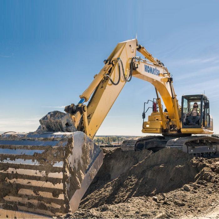 Yellow Komatsu digging gravel pit.