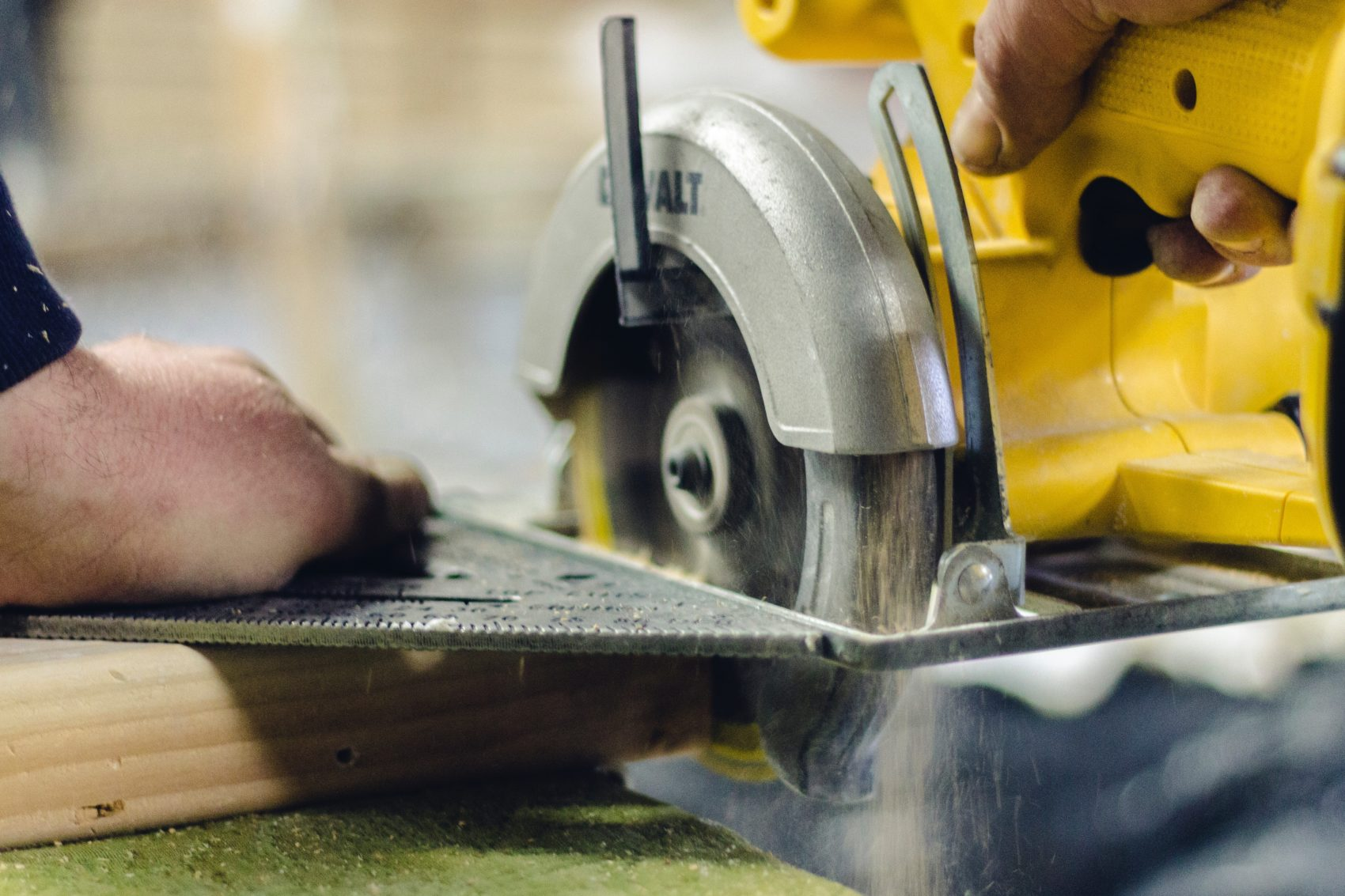 Worker using a yellow saw to cut.