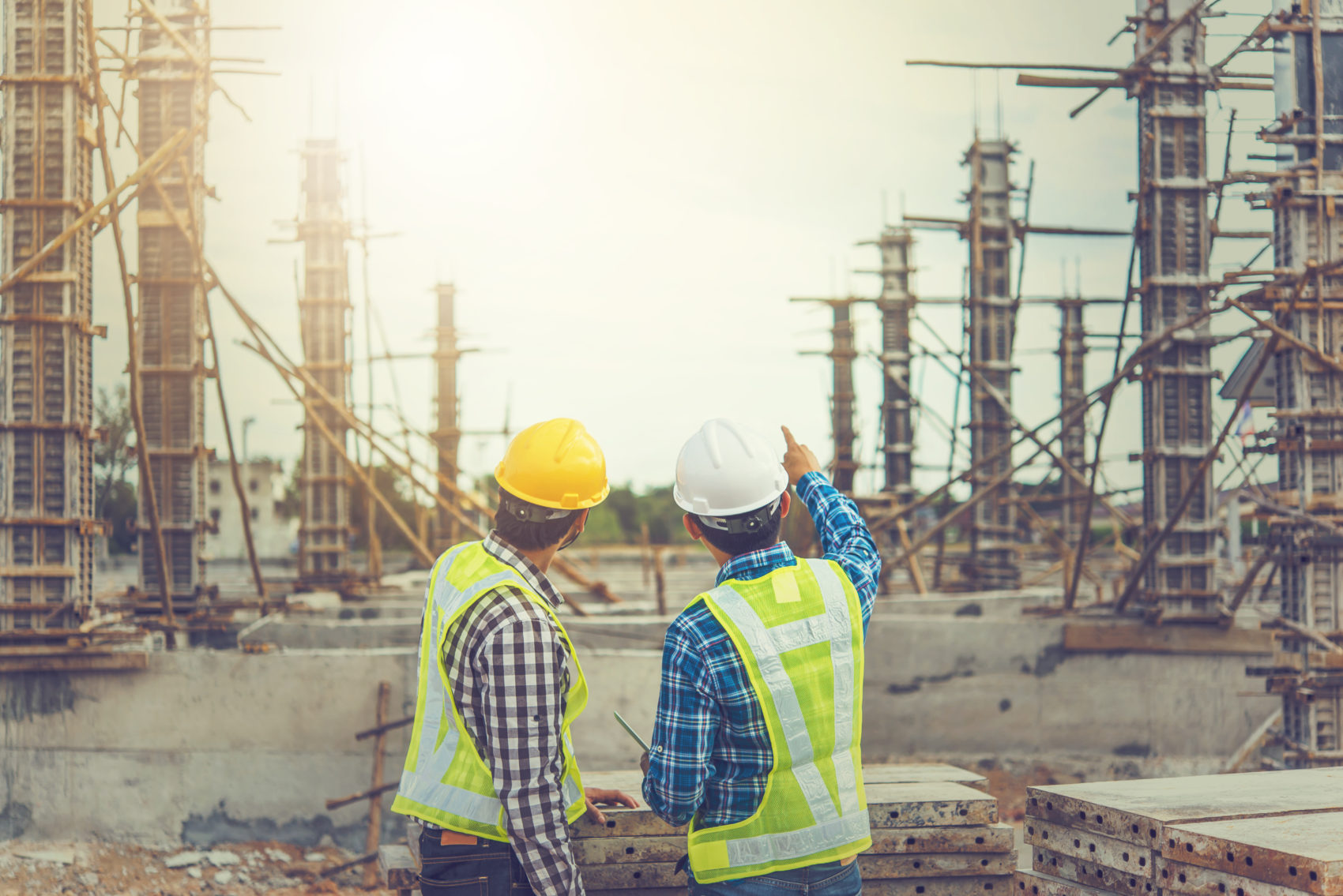 Two constructions workers pointing at job site.