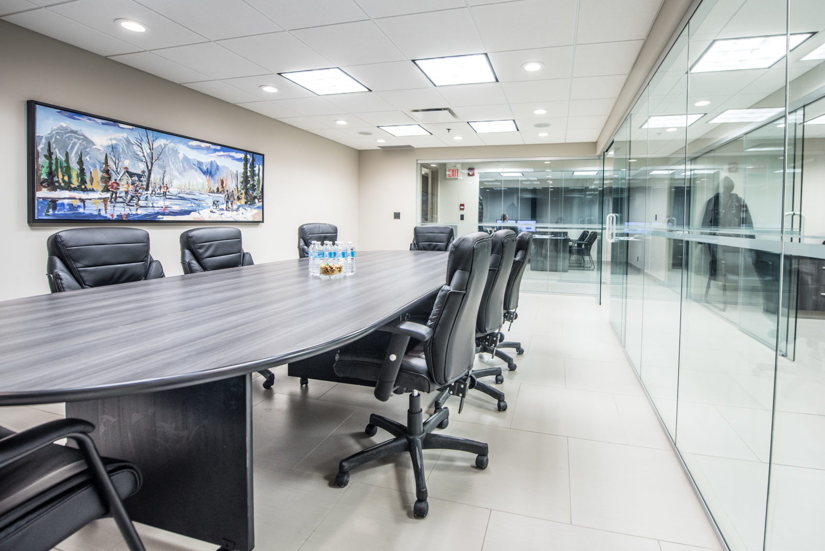 Boardroom office with flatscreen and glass walls.