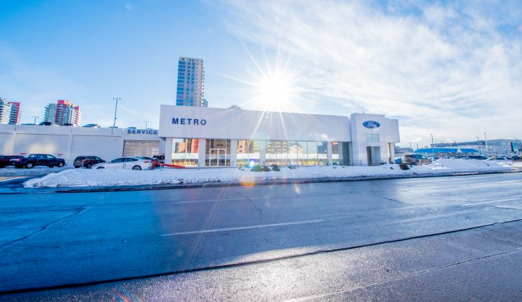 Exterior white building with snow on the ground at Metro Ford.