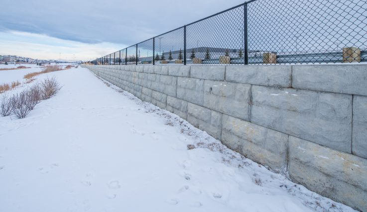 Black fence with retaining wall covered in snow at South Trail Auto Mall.