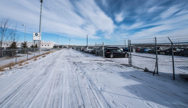 View through chain link fence of Stoney Trail Auto Storage.